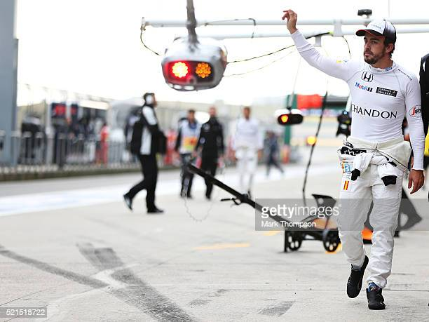 Fernando Alonso of Spain and McLaren Honda waves to the crowd from the pitlane during qualifying for the Formula One Grand Prix of China at Shanghai...