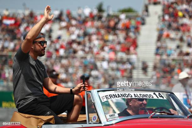 Fernando Alonso of Spain and McLaren Honda waves to the crowd on the drivers parade during the Canadian Formula One Grand Prix at Circuit Gilles...