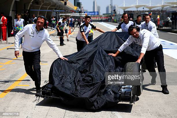 Fernando Alonso of Spain and McLaren Honda's car is pushed back to the garage by members of hie team during final practice for the Formula One Grand...