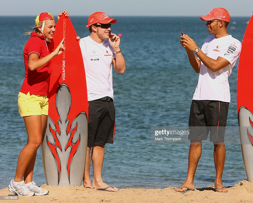 Fernando Alonso of Spain and McLaren Mercedes has his picture taken by team mate Lewis Hamilton of Great Britain as they pose with models dressed as...
