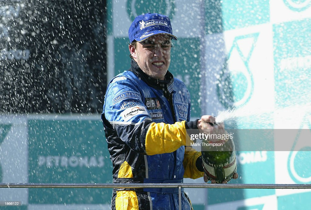 Fernando Alonso of Spain and Renault celebrates his third place and becoming the first Spainiard on the podium during the Malaysian Grand Prix at the Sepang International Circuit in Kuala Lumpur, Malaysia on March 23, 2003.