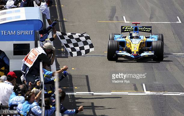 Fernando Alonso of Spain and Renault crosses the finish line first during the British F1 Grand Prix at Silverstone Circuit on June 11 2006 in...