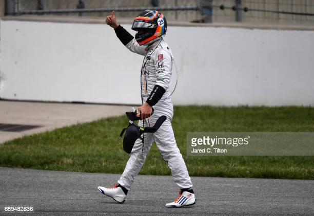 Fernando Alonso of Spain driver of the McLarenHondaAndretti Honda walks away from his car after his engine expired during the 101st Indianapolis 500...