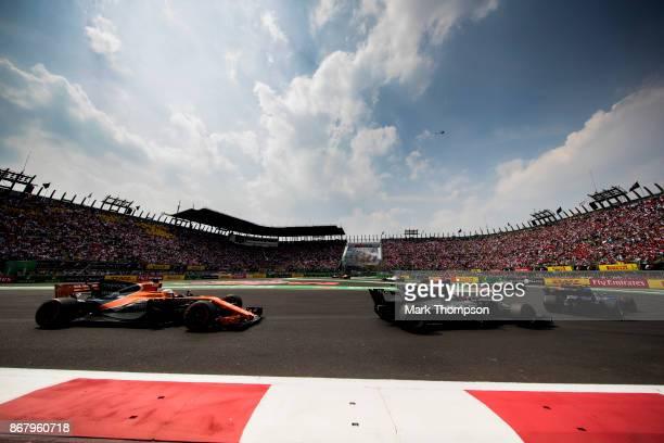 Fernando Alonso of Spain driving the McLaren Honda Formula 1 Team McLaren MCL32 follows Romain Grosjean of France driving the Haas F1 Team...