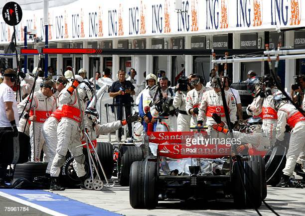 Fernando Alonso of Spain sits in front of Lewis Hamilton of Great Britain and McLaren Mercedes in the pits during the Hungarian Formula One Grand...