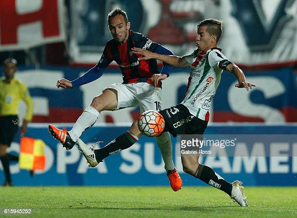 Fernando Belluschi of San Lorenzo fights for the ball with Agustin Farias of Palestino during a first leg match between San Lorenzo and Palestino as...