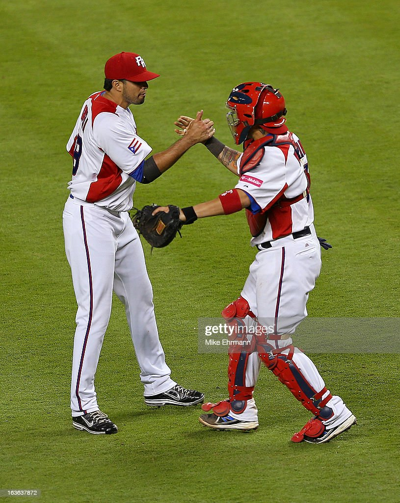 Fernando Cabrera #38 and <a gi-track='captionPersonalityLinkClicked' href=/galleries/search?phrase=Yadier+Molina&family=editorial&specificpeople=172002 ng-click='$event.stopPropagation()'>Yadier Molina</a> #4 of Puerto Rico celebrates after winning a World Baseball Classic second round game against Italy at Marlins Park on March 13, 2013 in Miami, Florida.