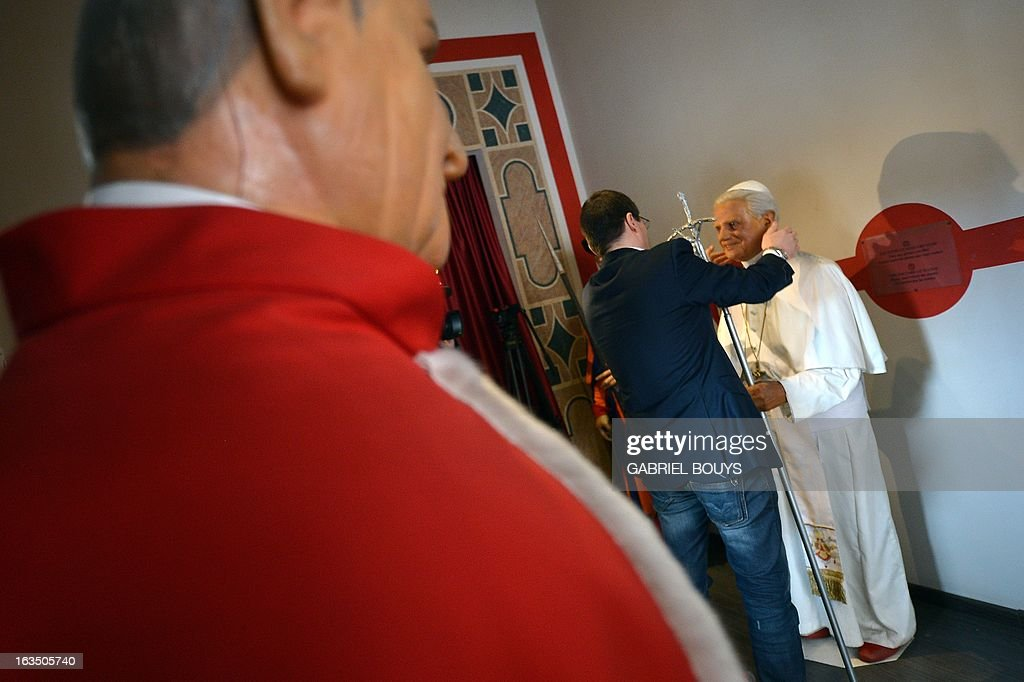 Fernando Canini (C), administrator of Rome wax museum, takes care of the statue of Pope Benedict XVI at the museum on March 11, 2013 in Rome. Catholic cardinals had a final day of jockeying for position today before shutting themselves into the Sistine Chapel to elect a new pope after Benedict XVI's shock resignation, with an Italian and a Brazilian who both head powerful archdioceses among the top contenders.