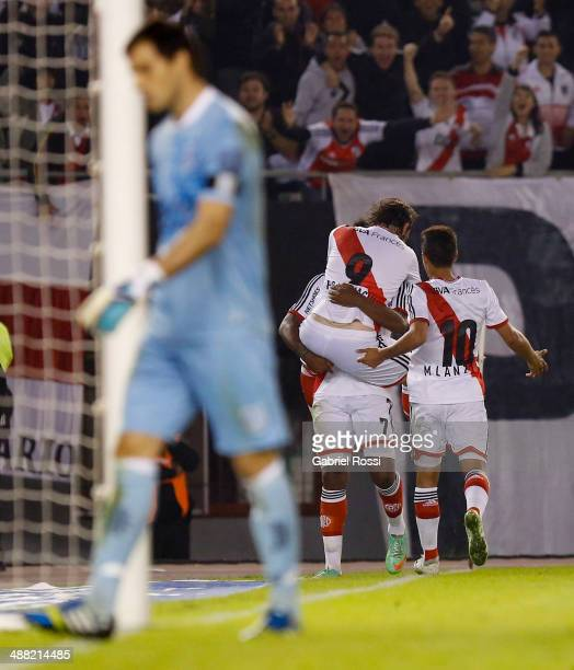 Fernando Cavenaghi of River Plate celebrates with Carlos Carbonero and Manuel Lanzini after scoring his team's third goal during a match between...