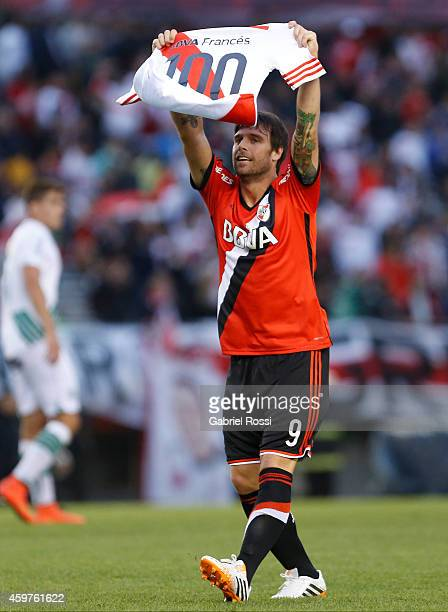 Fernando Cavenaghi of River Plate shows a jersey of River Plate with the number 100 on it to celebrate his 100th goal during a match between Banfield...