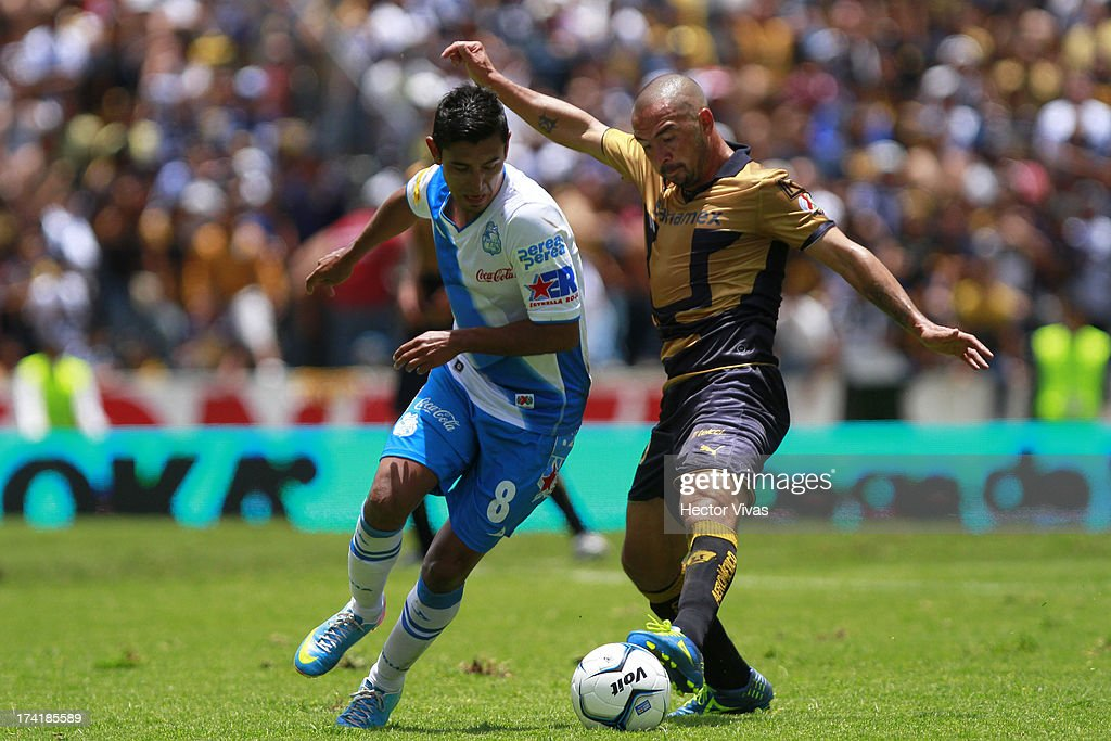 Fernando Espinosa (R) of Pumas struggles for the ball with Alberto Medina (L) of Puebla during a match between Pumas and Puebla as part of the Torneo Apertura 2013 Liga Mx at Cuauhtemoc Stadium on July 21, 2013 in Puebla, Mexico.