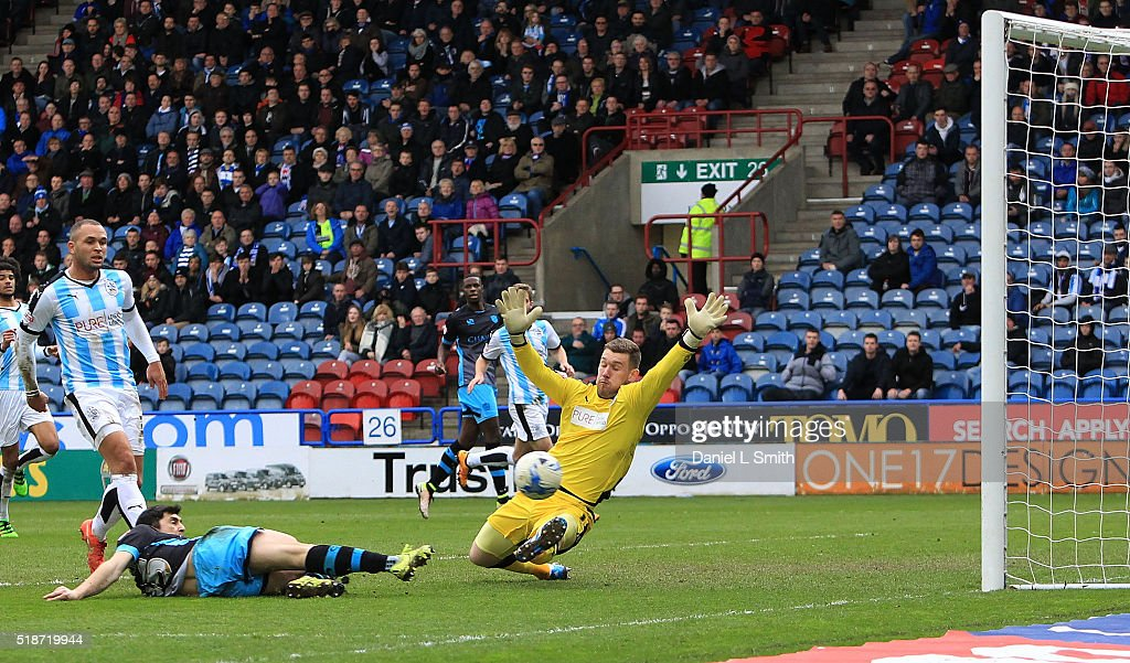 Fernando Forestieri of Sheffield Wednesday FC slips the ball past Jed Steer of Huddersfield Town FC to score the opening goal during the Sky Bet Championship match between Huddersfield Town and Sheffield Wednesday at Galpharm Stadium on April 2, 2016 in Huddersfield, United Kingdom.