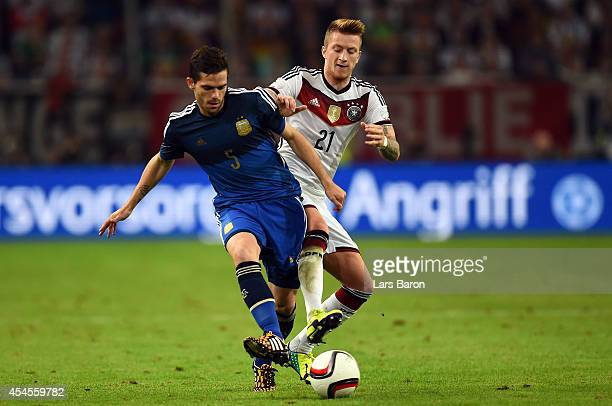 Fernando Gago of Argentina is challenged by Marco Reus of Germany during the international friendly match between Germany and Argentina at...
