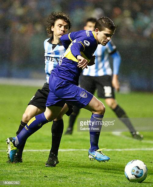 Fernando Gago of Boca Juniors fights for the ball with Agustin Pelletieri of Racing Club during a match between Boca Juniors and Racing Club as part...