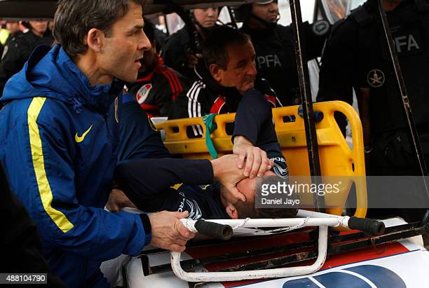 Fernando Gago of Boca Juniors is carried out the field after being injured during a match between River Plate and Boca Juniors as part of 24th round...