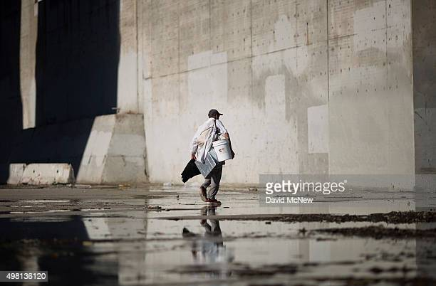 Fernando Lopez carries possessions along the Los Angeles River on November 20 2015 in Los Angeles California With the approach of devastating winter...