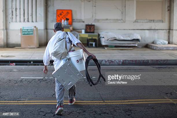 Fernando Lopez carries possessions to his street side encampment which is protected from minor storms by an overpass on November 20 2015 in Los...