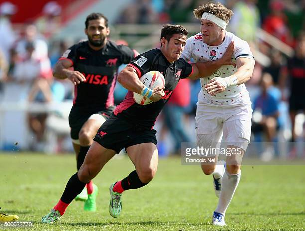 Fernando Luna of Argentina evades a tackle by Phil Burges of England during the Emirates Dubai Rugby Sevens HSBC World Rugby Sevens Series Cup...