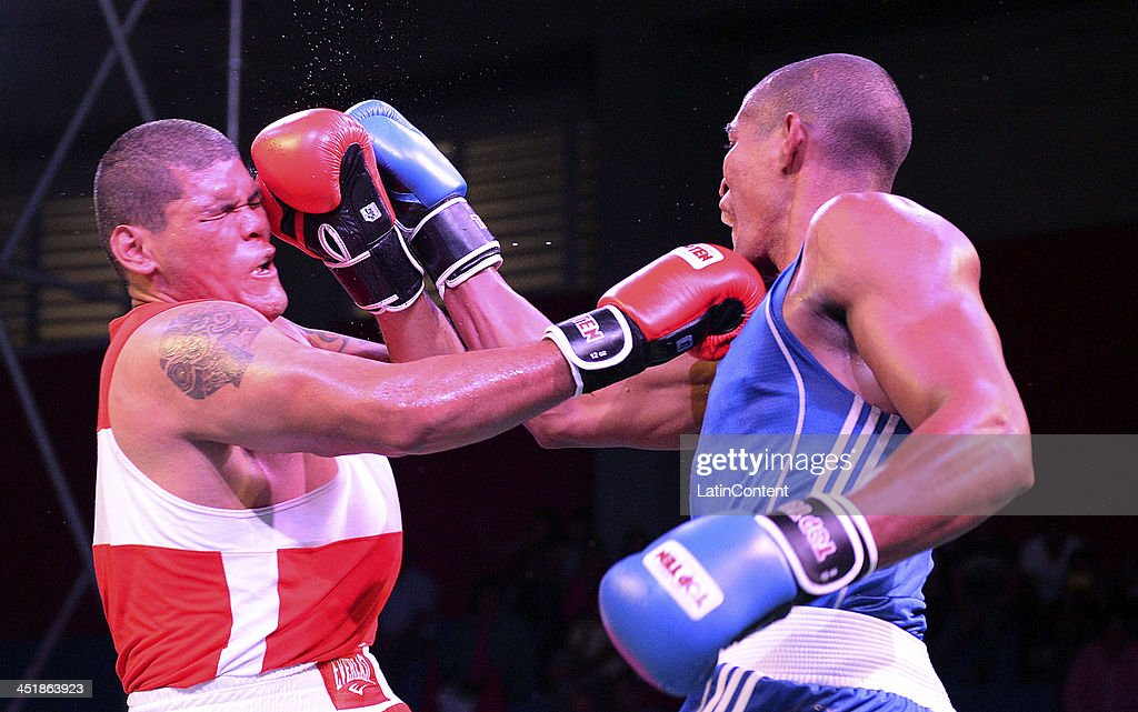 Fernando Muñoz of Peru (RED) fights with <a gi-track='captionPersonalityLinkClicked' href=/galleries/search?phrase=Jose+Payares&family=editorial&specificpeople=4436181 ng-click='$event.stopPropagation()'>Jose Payares</a> of Venezuela (BLUE) in Men's +91 kg as part of the XVII Bolivarian Games Trujillo 2013 at Colegio Nuestra Señora del Rosario on November 24, 2013 in Chiclayo, Peru.