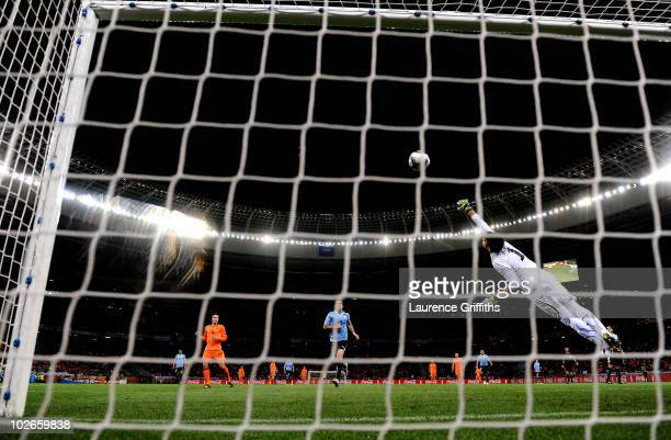 Fernando Muslera of Uruguay attempts to save the shot by Giovanni Van Bronckhorst of the Netherlands as he scores the opening goal during the 2010...