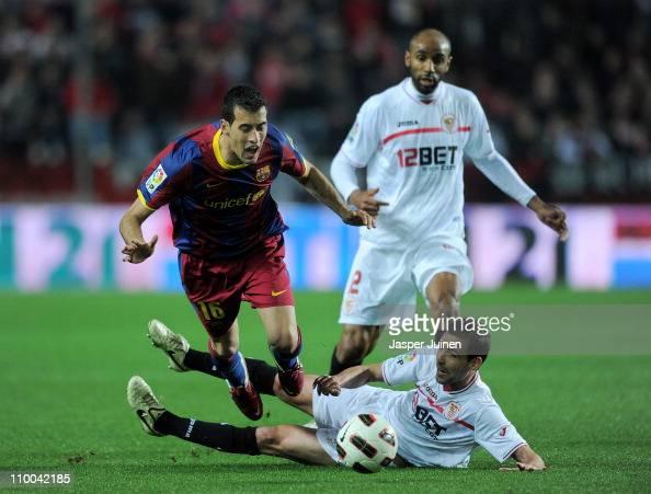 Fernando Navarro of Sevilla fouls Sergio Busquets of Barcelona during the la Liga match between Sevilla and Barcelona at Estadio Ramon Sanchez...