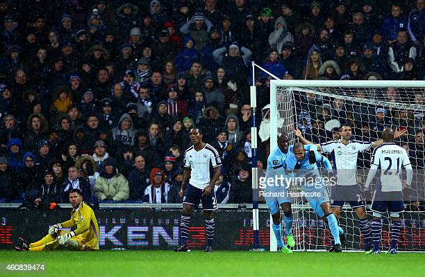 Fernando of Manchester City celebrates with teammate Eliaquim Mangala after scoring the opening goal during the Barclays Premier League match between...