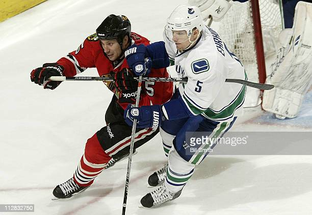 Fernando Pisani of the Chicago Blackhawks and Christian Ehrhoff of the Vancouver Canucks skate toward the puck in Game Three of the Western...