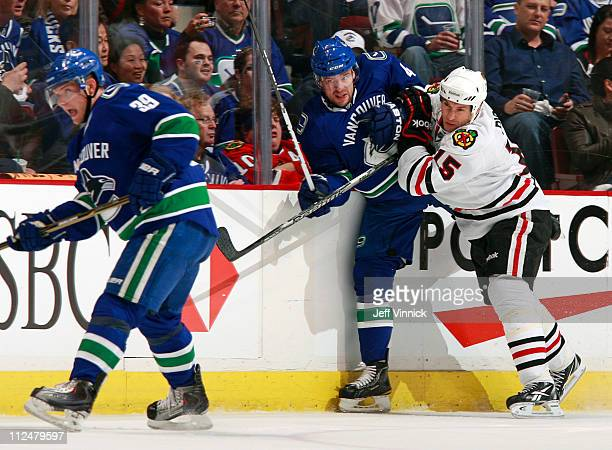 Fernando Pisani of the Chicago Blackhawks checks Keith Ballard of the Vancouver Canucks into the boards behind Cody Hodgson of the Canucks in Game...