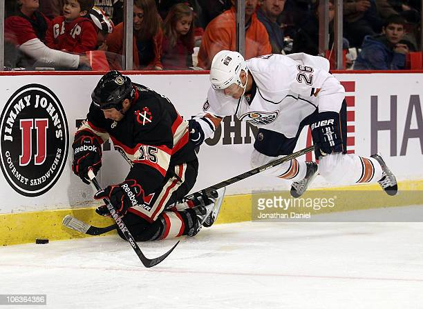 Fernando Pisani of the Chicago Blackhawks dives for the puck as Kurtis Foster of the Edmonton Oilers hops off the ice with his stick between Pisani's...