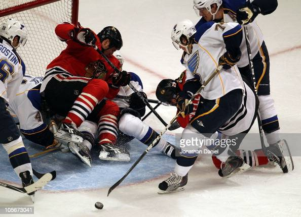 Fernando Pisani of the Chicago Blackhawks falls on Jaroslav Halak and Carlo Colaiacovo of the St Louis Blues as teammate Bryan Bickell tries to shoot...