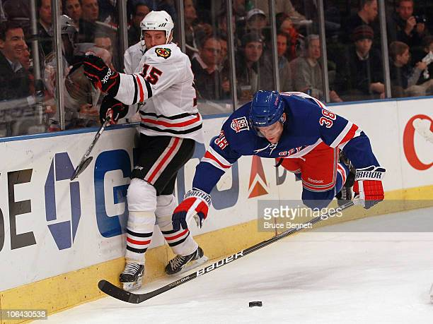 Fernando Pisani of the Chicago Blackhawks hits the boards as Michael Sauer of the New York Rangers trips at Madison Square Garden on November 1 2010...