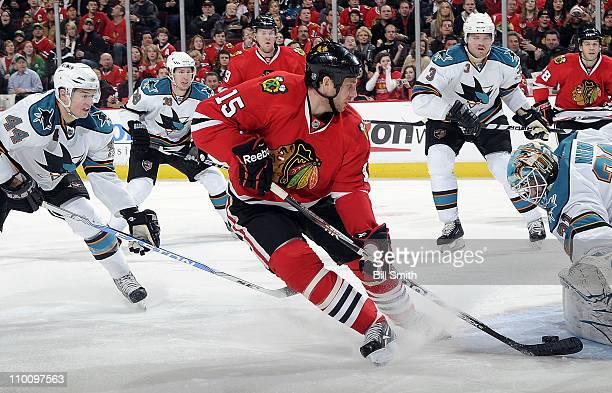 Fernando Pisani of the Chicago Blackhawks takes the puck toward San Jose Sharks' goalie Antti Niemi as MarcEdouard Vlasic of the Sharks follows...
