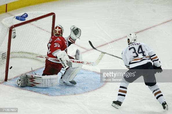 Fernando Pisani of the Edmonton Oilers scores a short handed game winning goal past goaltender Cam Ward of the Carolina Hurricanes in game five of...