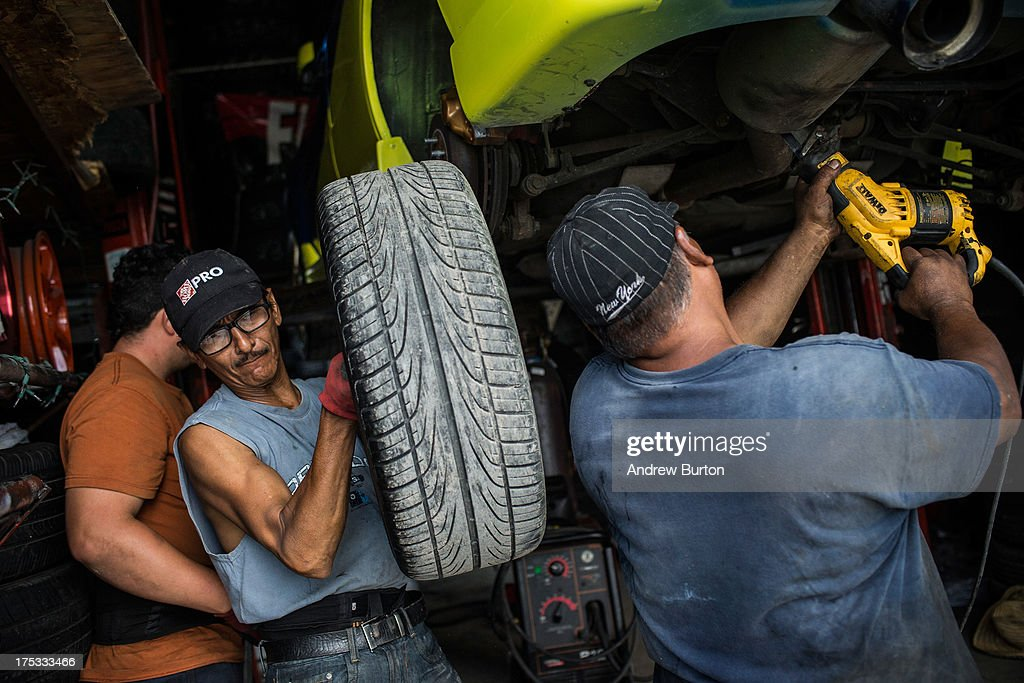 Fernando Ramirez (C) removes a tire from a car on August 2, 2013 in the Willet's Point neighborhood of the Queens borough of New York City. The neighborhood has been in a battle with the city of New York for years, which plans to demolish the neighborhood and invest $3 billion for a mall, apartments and more parking for nearby Citi Field. Members of the neighborhood argue that over two hundred small businesses are established in the neighborhood and should not be evicted.