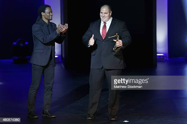 Fernando Reis poses with the Weightlifting Athlete of the Year Trophy as Toni Garrido applauds during the Brazil Olympics Awards Ceremony at Theatro...