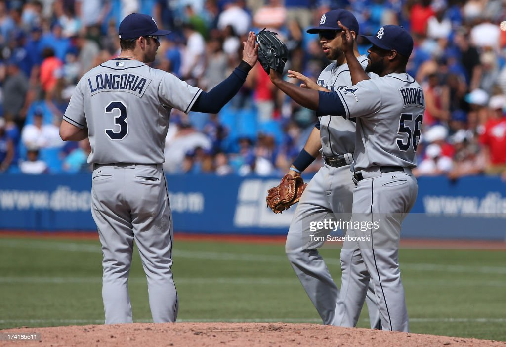 <a gi-track='captionPersonalityLinkClicked' href=/galleries/search?phrase=Fernando+Rodney&family=editorial&specificpeople=547291 ng-click='$event.stopPropagation()'>Fernando Rodney</a> #56 of the Tampa Bay Rays celebrates their victory with <a gi-track='captionPersonalityLinkClicked' href=/galleries/search?phrase=Evan+Longoria&family=editorial&specificpeople=2349329 ng-click='$event.stopPropagation()'>Evan Longoria</a> #3 and <a gi-track='captionPersonalityLinkClicked' href=/galleries/search?phrase=James+Loney&family=editorial&specificpeople=636293 ng-click='$event.stopPropagation()'>James Loney</a> #21 during MLB game action against the Toronto Blue Jays on July 21, 2013 at Rogers Centre in Toronto, Ontario, Canada.