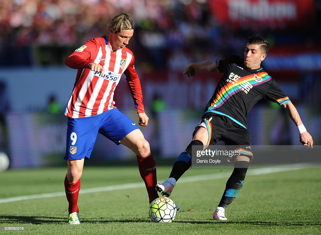Fernando Toirres of Club Atletico de Madrid is taciled by heads the ball beside Adrian Embarba of Rayo Vallecano during the La Liga match between Club Atletico de Madrid and Rayo Vallecano at Vicente Calderon Stadium on April 30, 2016 in Madrid, Spain.