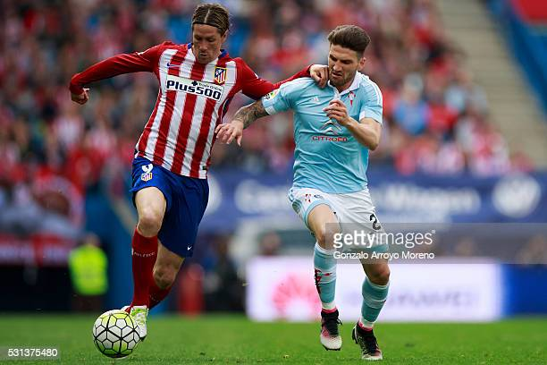 Fernando Torres of Atletico de Madrid competes for the ball with Carles Planas of RC Celta de Vigo during the La Liga match between Club Atletico de...