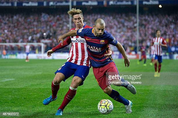 Fernando Torres of Atletico de Madrid competes for the ball with Javier Alejandro Mascherano of FC Barcelona during the La Liga match between Club...