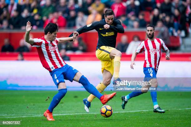 Fernando Torres of Atletico Madrid duels for the ball with Jorge Mere of Real Sporting de Gijon during the La Liga match between Real Sporting de...
