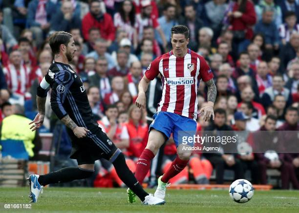 Fernando Torres of Atletico Madrid in action against Sergio Ramos of Real Madrid during the UEFA Champions League semi final second leg match between...