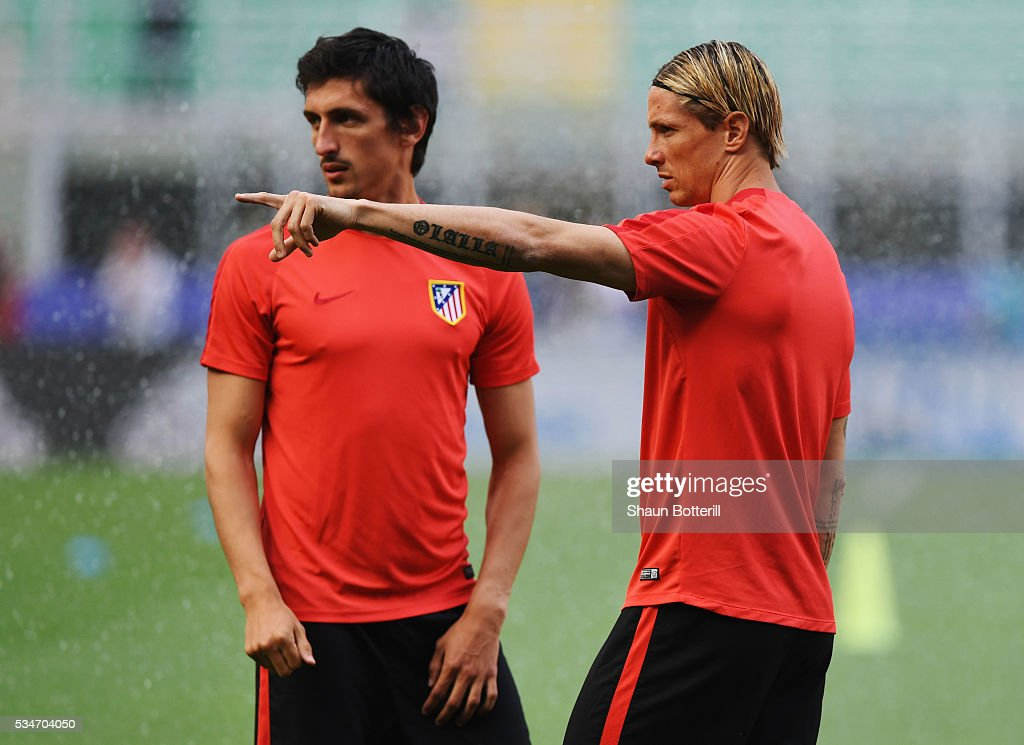 Fernando Torres of Atletico Madrid talks with Stefan Savic of Atletico Madrid during an Atletico de Madrid training session on the eve of the UEFA Champions League Final against Real Madrid at Stadio Giuseppe Meazza on May 27, 2016 in Milan, Italy.