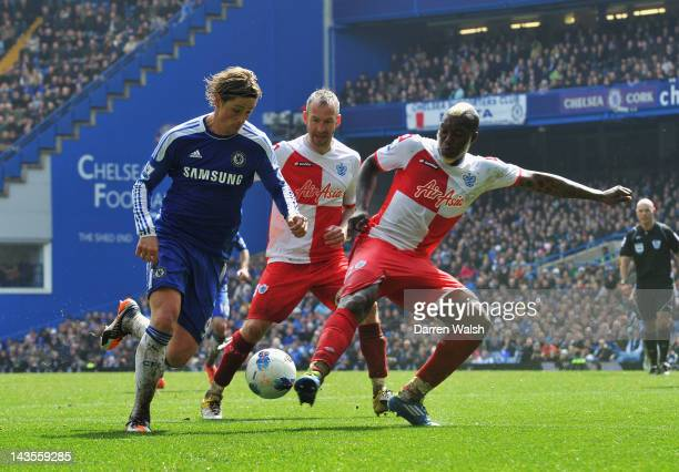 Fernando Torres of Chelsea is challenged by Djibril Cisse of Queens Park Rangers during the Barclays Premier League match between Chelsea and Queens...