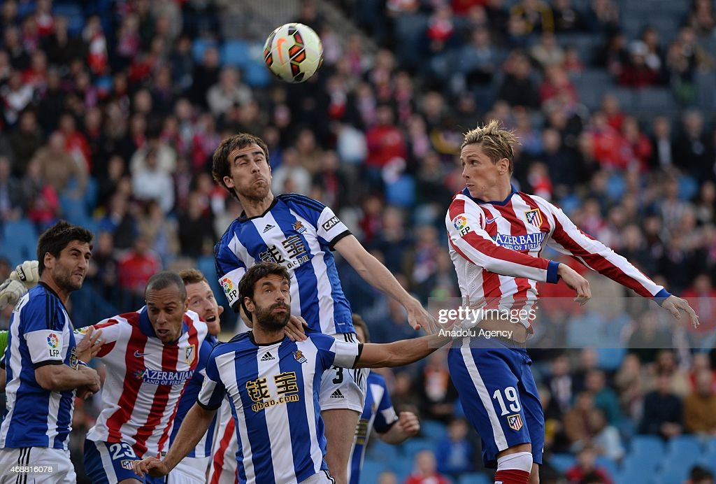 Fernando Torres of Club Atletico de Madrid and Mikel Gonalez of Real Sociedad rise for a high ball during the La Liga match between Club Atletico de...