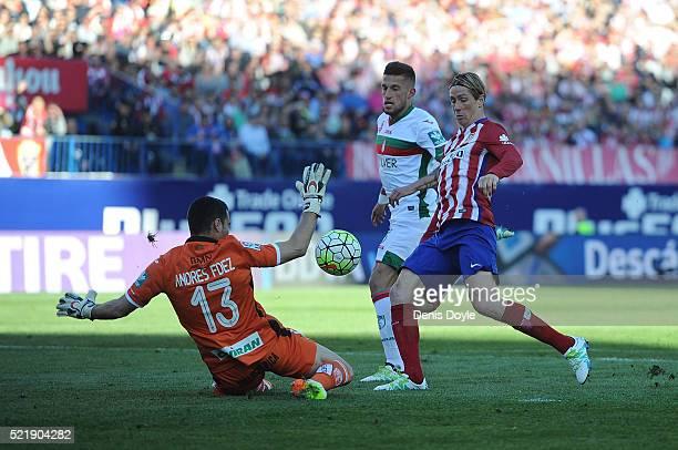 Fernando Torres of Club Atletico de Madrid beats Andres Fernandez of Granada to score his team's 2nd goal during the La Liga match between Club...