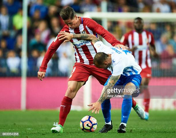 Fernando Torres of Club Atletico de Madrid competes for the ball with Sandro Ramirez of Malaga CF during La Liga match between Malaga CF and Club...