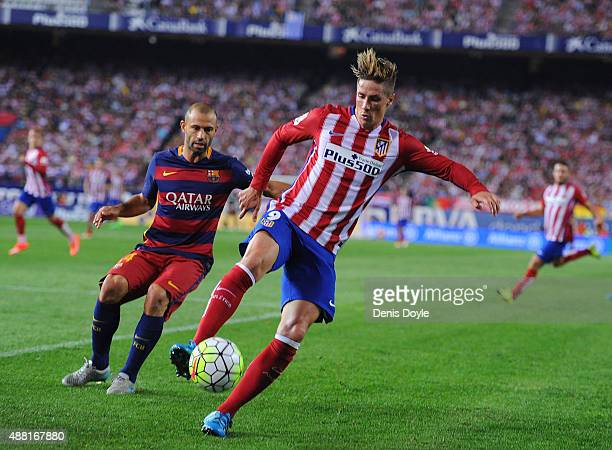Fernando Torres of Club Atletico de Madrid in action beside Javier Mascherano of FC Barcelona during the La Liga match between Club Atletico de...