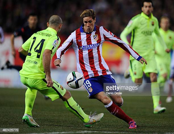 Fernando Torres of Club Atletico de Madrid tries to dribble the ball past Javier Mascherano of FC Barcelona during the Copa del Rey Quarter Final...