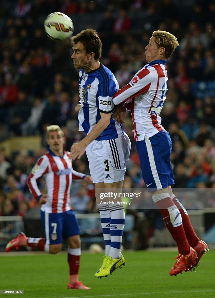 Fernando Torres of Club Atletico de Madrid vies for ball with Mikel Gonzalez of Real Sociedad during the La Liga match between Club Atletico de...