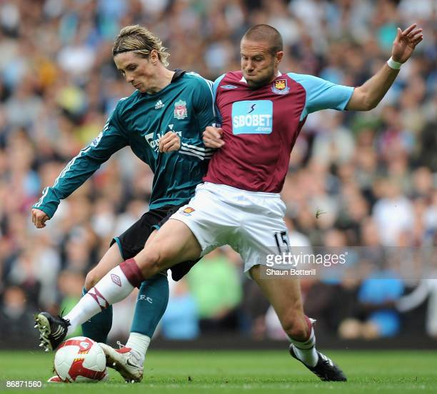 Fernando Torres of Liverpool and Matthew Upson of West Ham battle for the ball during the Barclays Premier League match between West Ham United and...